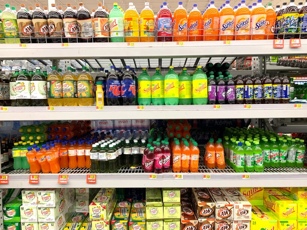 Supermarket shelves stacked with bottles of sugary soda drinks