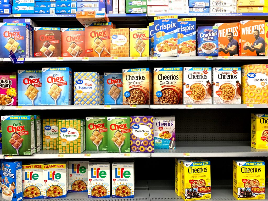 Supermarket shelves stacked with boxes of sugary cereals